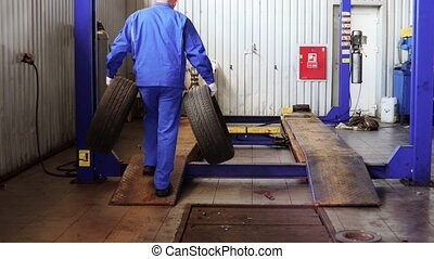 male mechanic carry worn tires. Storing used tires for winter season.