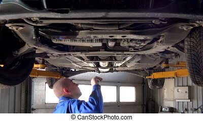 Male mechanic examining lifted automobile parts at auto...