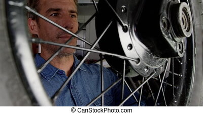 Male mechanic examining motorcycle wheel in repair garage 4k