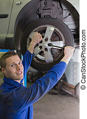 Male mechanic fixing car tire with wrench