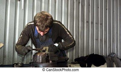 male mechanic grind rusty metal with rasp tool in garage.