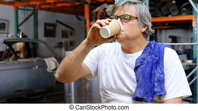 Male mechanic having coffee 4k - Male mechanic having coffee...