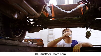 Male mechanic having coffee while servicing a car 4k - Male...