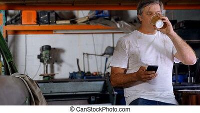 Male mechanic having coffee while using mobile phone 4k