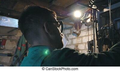 Male mechanic in glasses fixes car detail. Man in workwear...