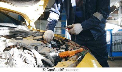 Male mechanic in gloves checks electric components in hood of the car - automobile service diagnostics