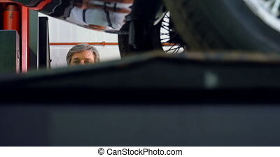 Male mechanic operating car lift 4k - Male mechanic ...