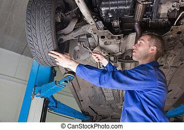 Male mechanic repairing car