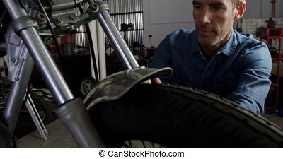 Male mechanic repairing motorbike in repair garage 4k