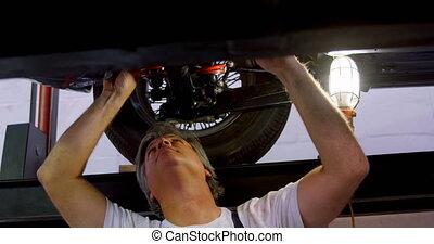 Male mechanic servicing a car 4k - Male mechanic servicing a...