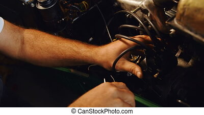 Male mechanic servicing a car in garage 4k - Close-up of...