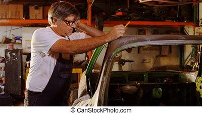 Male mechanic talking on mobile phone 4k