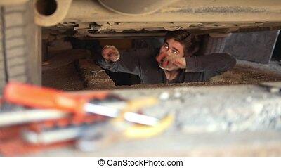 Male mechanic underneath a car repairs his car in garage,...
