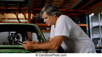 Male mechanic using mobile phone 4k