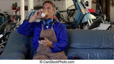 Male mechanic using mobile phone in motorbike repair garage ...