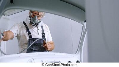 Male mechanic using spray paint 4k