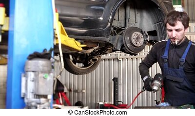 male mechanic with cigarette repairing car brake system