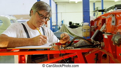 Male mechanic writing on clipboard 4k - Male mechanic...