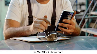 Male mechanic writing on clipboard while using mobile phone 4k