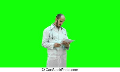 Male medicine doctor checking his papers on a Green Screen, Chroma Key.