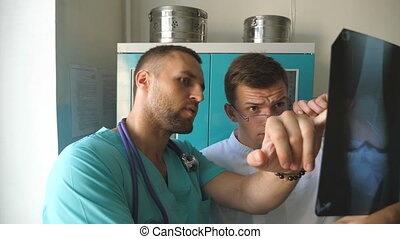 Male medics consult with each other while looking at x ray...