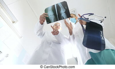 Male medics consult with each other while looking at x ray image. Two caucasian doctors view mri picture and discussing about it. Medical workers in hospital examine x-ray prints. Low angle of view