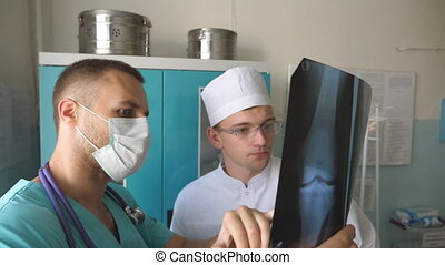 Male medics consult with each other while looking at x ray image. Two caucasian doctors view mri picture and discussing about it. Medical workers in hospital examine x-ray prints. Close up Slow motion