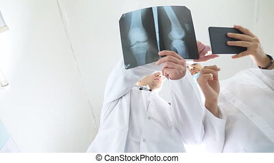 Male medics using tablet pc while consult with each other about x ray image of patient. Medical workers in hospital examine x-ray prints. Two caucasian doctors view mri picture and discussing about it
