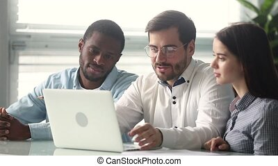 Male mentor talking teaching diverse interns pointing on laptop