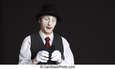 male MIME looking for money in purse on a black background....