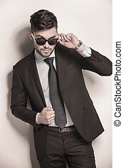 male model in suit and tie taking off his sunglasses