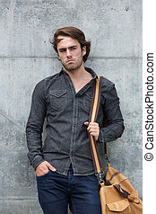 Male model posing with leather travel bag