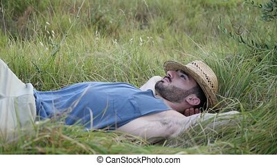 Male model relaxing, laid down in a field