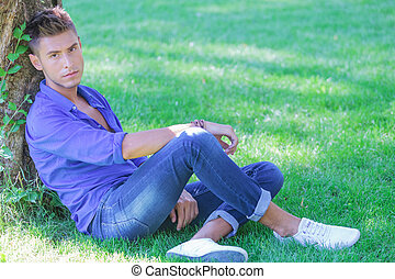 male model sitting next to tree
