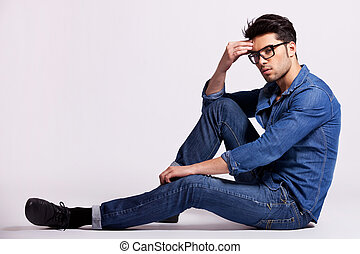male model sitting on grey background and thinking