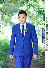 Male model, the groom portrait in a blue suit with a boutonniere among the green foliage on a wedding day.