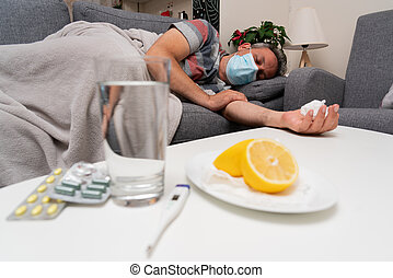 Sick male model wearing surgical or medical protective mask to prevent contamination sleeping on sofa cold sars covid19 treatment pills water thermometer and citrus fruit as immunity vitaminc concept