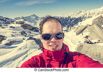 Male mountaineering taking a selfie high in the mountains.