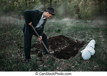 Male murderer with a shovel is digging a grave