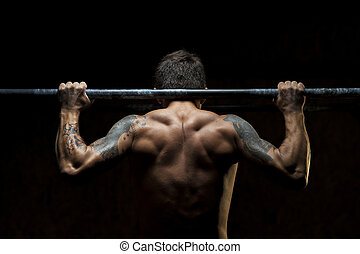 Male muscular athlete doing pull up exercise