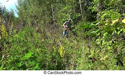 male mushroom picker looking for mushrooms. Man carry basket...