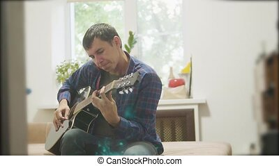Male musician playing acoustic guitar lifestyle. man playing acoustic guitar slow motion video. in the room sits on the couch. man and guitar concept