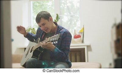 Male musician playing acoustic guitar. lifestyle man playing acoustic guitar slow motion video. in the room sits on the couch. man and guitar concept