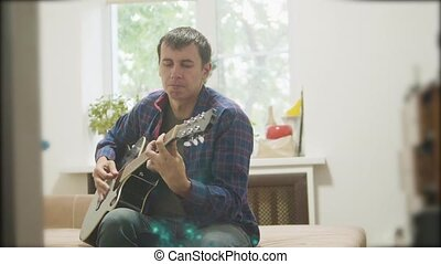 Male musician playing acoustic guitar. man lifestyle playing acoustic guitar slow motion video. in the room sits on the couch. man and guitar concept
