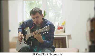 Male musician playing acoustic guitar. man playing acoustic guitar lifestyle slow motion video. in the room sits on the couch. man and guitar concept