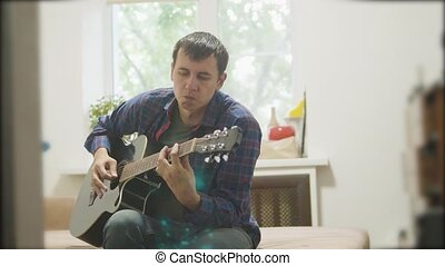 Male musician playing acoustic guitar. man playing acoustic guitar slow lifestyle motion video. in the room sits on the couch. man and guitar concept