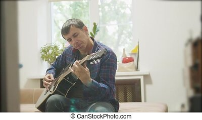Male musician playing acoustic guitar. man playing acoustic guitar slow motion lifestyle video. in the room sits on the couch. man and guitar concept