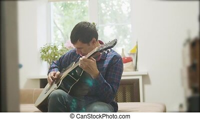 Male musician playing acoustic guitar. man playing acoustic guitar slow motion video. in the room sits on the couch lifestyle. man and guitar concept