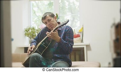 Male musician playing acoustic guitar. man playing acoustic guitar slow motion video. in the room lifestyle sits on the couch. man and guitar concept