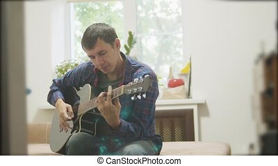 Male musician playing acoustic guitar. man playing acoustic guitar slow motion video. in the room sits on the couch. man and guitar concept lifestyle